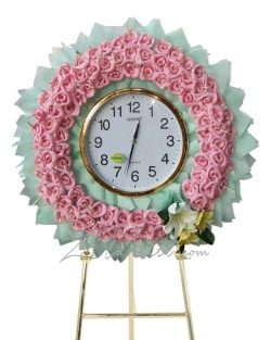 พวงหรีดสีเขียวมิ้นแบบนาฬิกา และดอกไม้สีชมพู