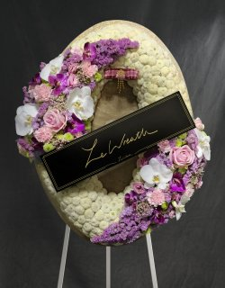 พวงหรีดดอกไม้สด ทรงวงรี โทนสีขาวและม่วง จากร้านเลอหรีด